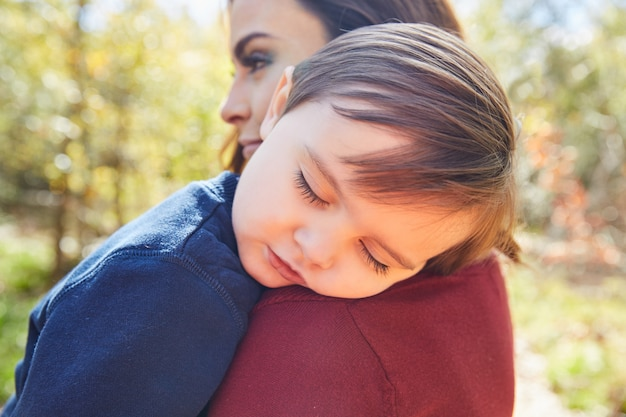 Mutterholdingkinderjunge, der in ihrer schulter schläft Premium Fotos