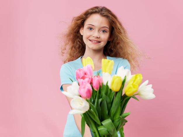 Muttertag, eine junge frau mit einem kind, das im studio mit blumen posiert, ein geschenk für frauentag und muttertag Premium Fotos