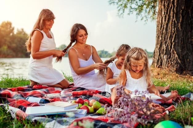 Muttertag. mutter, großmutter und kinder weben haarzöpfe miteinander. familie, die spaß während des picknicks hat Premium Fotos