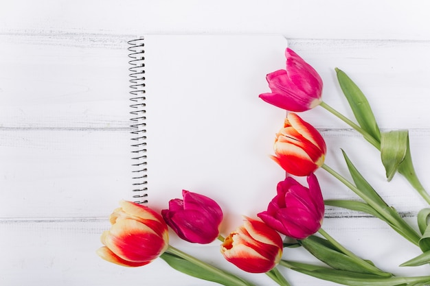 Muttertag. rosa tulpen und notizbuch mit exemplarplatz. Premium Fotos