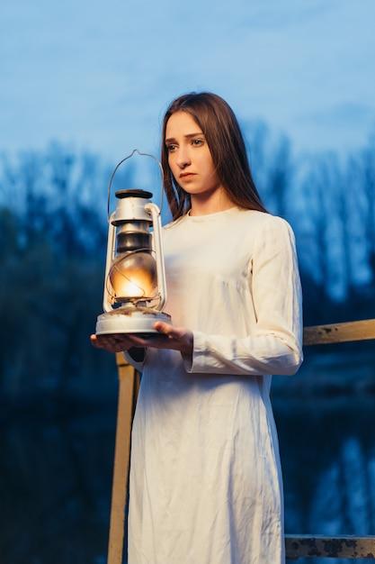 Mysteriöses mystisches mädchen in einem dunklen nachtwald mit einer kerosinlampe in ihren händen Premium Fotos