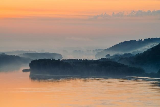 Mystischer dunst des morgens über breitem tal des flusses. goldglühen von der dämmerung im himmel. flussufer mit wald unter nebel. sonnenlicht spiegelt sich im wasser bei sonnenaufgang. bunte atmosphärische landschaft der majestätischen natur. Premium Fotos
