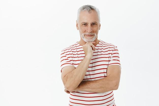 Nachdenklich lächelnder älterer mann im t-shirt, der mit erfreutem ausdruck schaut Kostenlose Fotos
