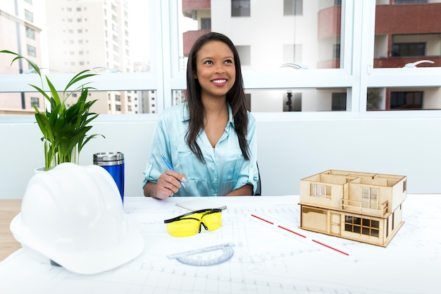 Nachdenkliche afroamerikanerdame auf stuhl nahe schutzhelm und modell des hauses auf tabelle Kostenlose Fotos
