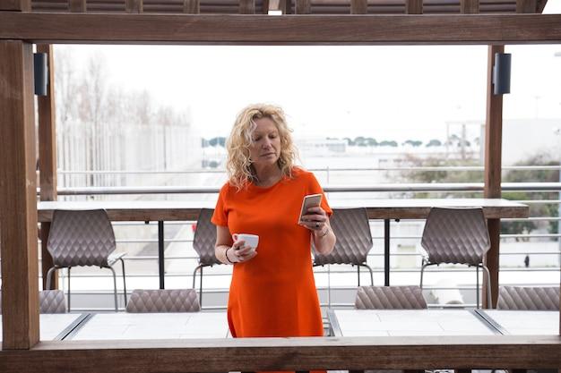 Nachdenkliche dame mit trinkendem kaffee des smartphone Kostenlose Fotos