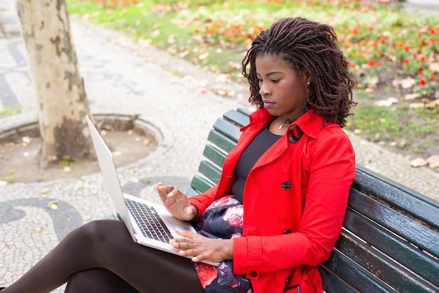 Nachdenkliche frau, die auf laptop schreibt, während sie auf bank im park sitzt Kostenlose Fotos