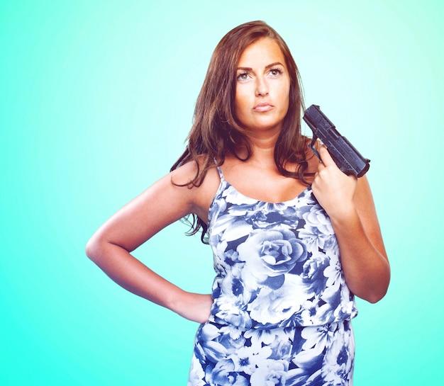 Nachdenkliche frau mit einer pistole Kostenlose Fotos