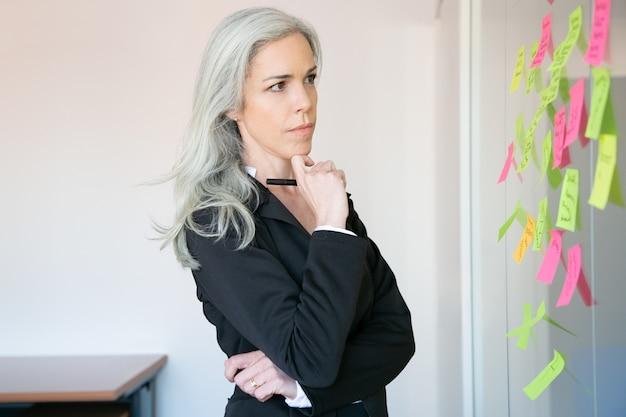 Nachdenkliche grauhaarige geschäftsfrau, die notizen auf glaswand liest und marker hält. konzentrierte kaukasische arbeiterin im anzug, die über die idee für ein projekt nachdenkt. Kostenlose Fotos