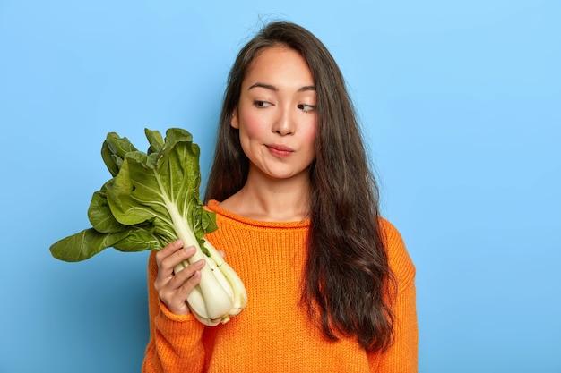 Nachdenkliche hausfrau hält green bok choy, überlegt, was sie aus diesem nützlichen gemüse kochen soll, hält sich an die diät, ist vegetarierin und trägt einen orangefarbenen pullover Kostenlose Fotos