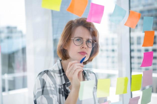 Nachdenkliche hipster frau, die in ihrem büro steht und notizen über alles liest Premium Fotos