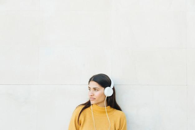 Nachdenkliche junge frau musik hören gegen weiße wand stehen Kostenlose Fotos