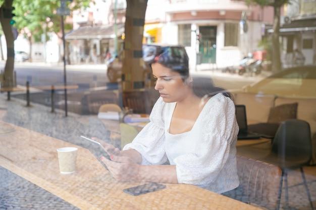 Nachdenkliche junge geschäftsfrau, die am schreibtisch im gemeinsamen arbeitsraum oder im kaffeehaus unter verwendung der tablette sitzt Kostenlose Fotos