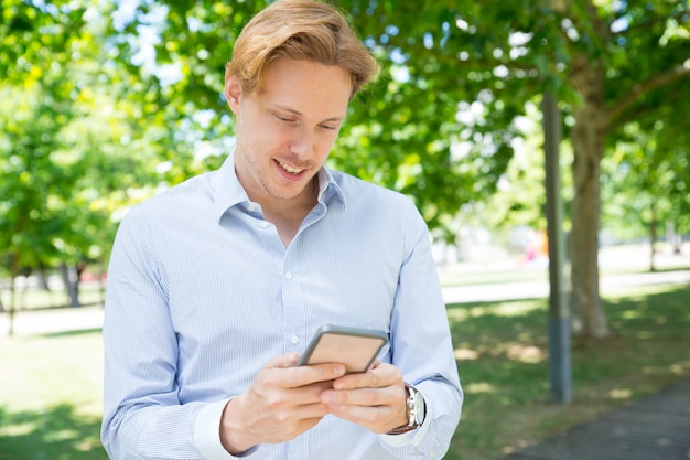Nachdenkliche lächelnde simsende mitteilung des kerls am telefon Kostenlose Fotos