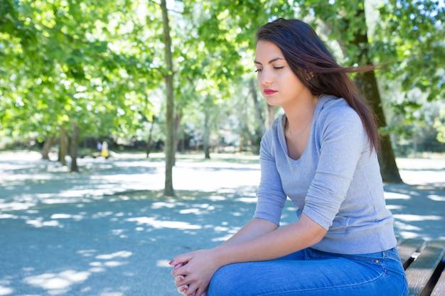 Nachdenkliche recht junge dame, die im park stillsteht Kostenlose Fotos
