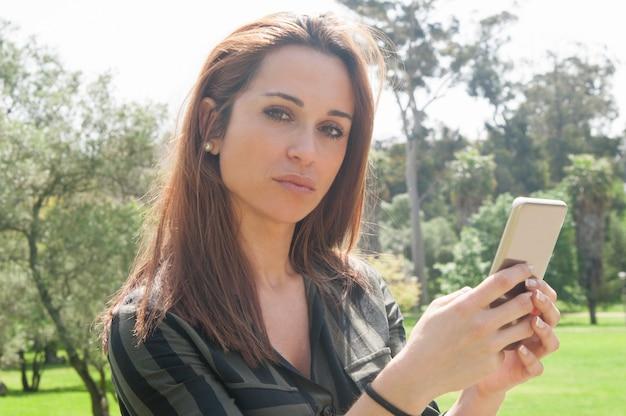 Nachdenkliche schöne dame, die draußen mobiltelefon verwendet Kostenlose Fotos