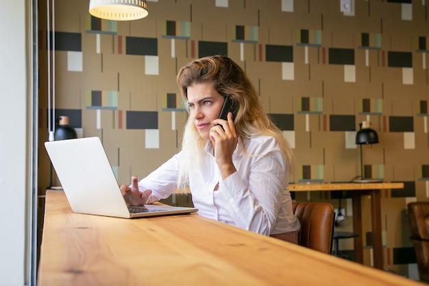 Nachdenkliche unternehmerin, die laptop verwendet und auf mobiltelefon im gemeinsamen arbeitsraum spricht Kostenlose Fotos