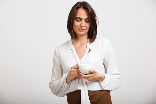 Nachdenkliche verärgerte modefrau trinkt kaffee und denkt nach Kostenlose Fotos