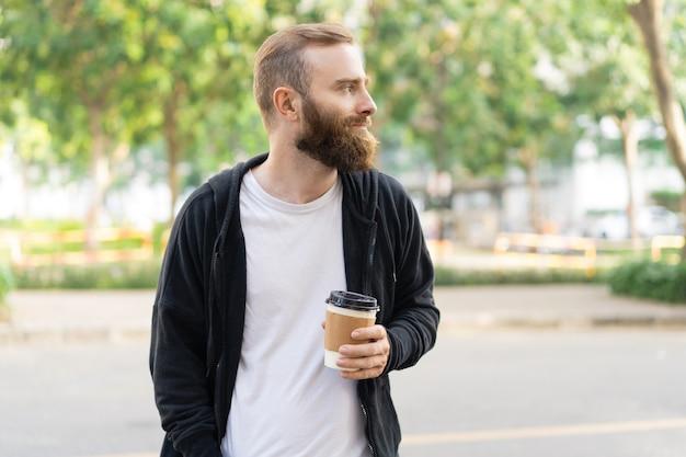 Nachdenklicher bärtiger mann, der in stadt geht und plastikschale hält Kostenlose Fotos