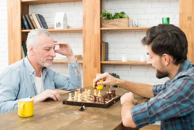 Nachdenklicher gealterter mann und junger kerl, die bei tisch schach im raum spielen Kostenlose Fotos