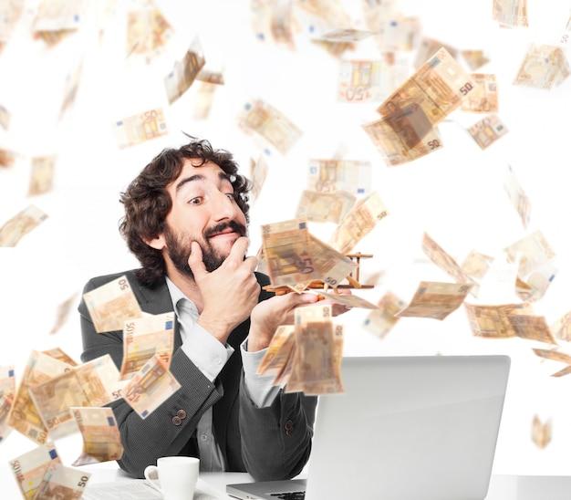 Nachdenklicher geschäftsmann unter einem geld regen Kostenlose Fotos