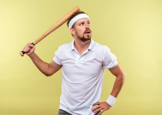 Nachdenklicher junger gutaussehender sportlicher mann, der stirnband und armbänder hält, die baseballschläger halten und hand auf taille setzen, die seite lokal auf grünfläche betrachtet Kostenlose Fotos