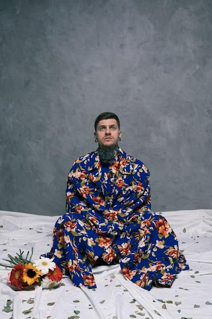 Nachdenklicher junger mann, der auf boden mit den gekreuzten beinen nahe den gerberablumen sitzt Kostenlose Fotos