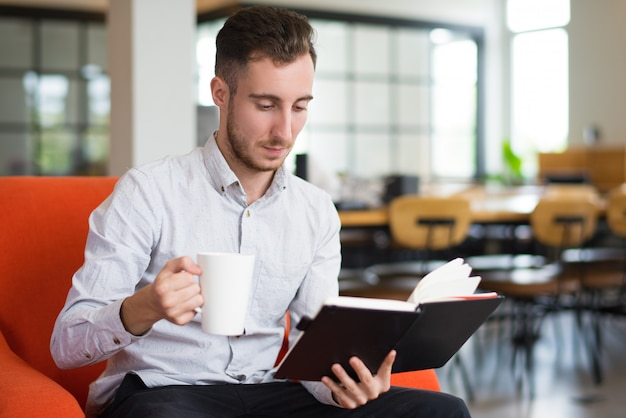 Nachdenklicher kaukasischer junger mann, der schale und lesung hält Kostenlose Fotos