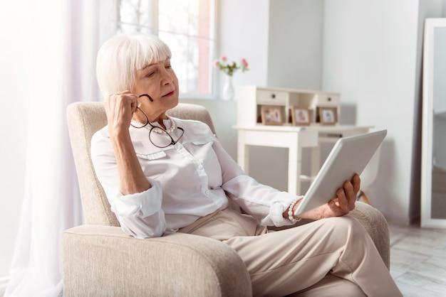 Nachdenklicher leser. angenehme ältere dame, die nachdenklich von einer tafel liest, nachdem sie ihre brille abgenommen hat, während sie im sessel sitzt Premium Fotos