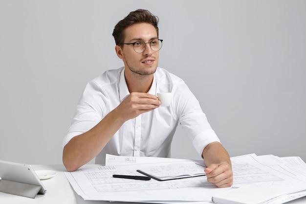 Nachdenklicher männlicher manager hält eine tasse kaffee, schaut nachdenklich in die ferne, plant seine zukünftigen aktionen, überlegt, wie man vorlagen auf webseiten zeichnet, hat großartige ideen. entwurfs- und konstruktionskonzept Kostenlose Fotos