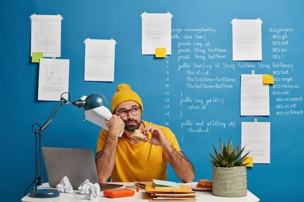 Nachdenklicher männlicher programmierer oder softwareentwickler denkt über programmcode nach, schaut weg und isst burger, hält papiere, trägt gelbe kleidung und verbringt zeit für die erstellung eines projekts. Kostenlose Fotos