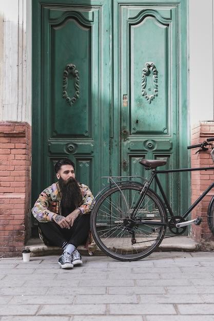 Nachdenklicher mann, der vor alter tür mit seinem fahrrad sitzt Kostenlose Fotos