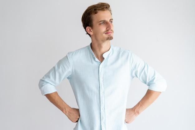 Nachdenklicher mann, der weg schaut und hände auf hüften hält Kostenlose Fotos