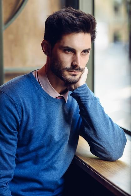 Nachdenklicher mann mit blauer strickjacke mit verlorenem blick nahe einem fenster Premium Fotos