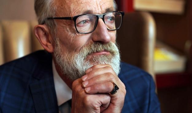 Nachdenklicher, müder, grausamer blick eines rentners, eines buchautors, eines graubärtigen alten mannes in einem schmalen anzug in einem schicken büro, interieur Premium Fotos