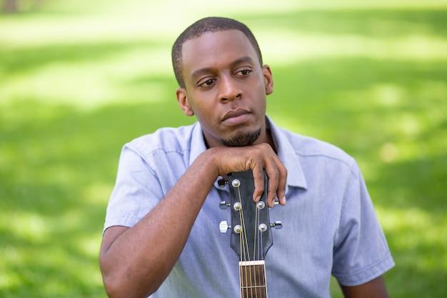Nachdenklicher schwarzer mann, der auf gitarre headstock im park sich lehnt Kostenlose Fotos