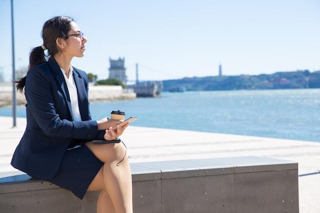 Nachdenkliches büromädchen, das arbeitspause genießt Kostenlose Fotos