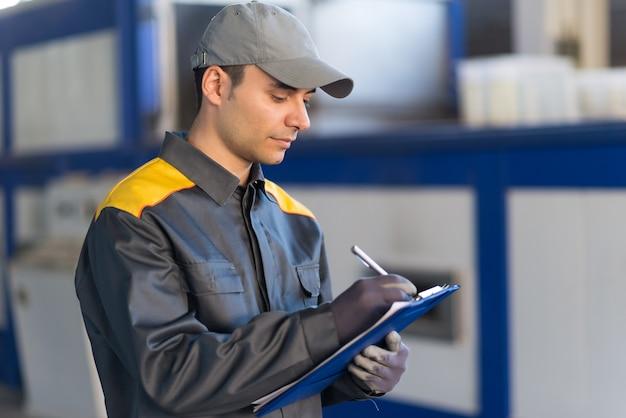 Nachdenkliches industriearbeiterschreiben auf einem dokument Premium Fotos