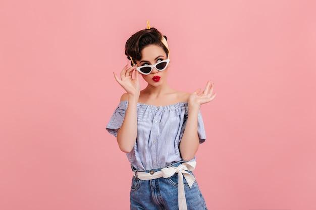Nachdenkliches pinup-mädchen in der sonnenbrille, die auf rosa hintergrund steht. studioaufnahme der brünetten jungen dame im sommeroutfit. Kostenlose Fotos
