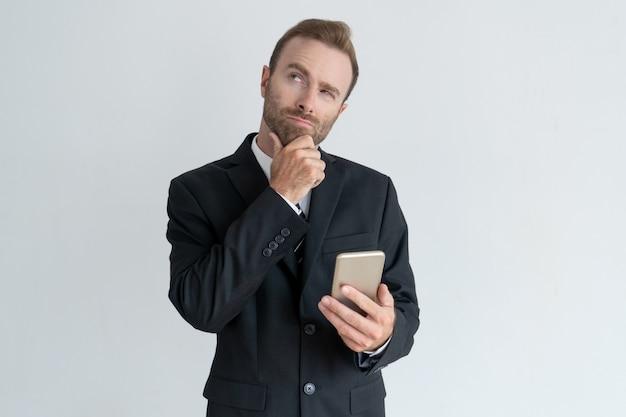 Nachdenkliches rührendes kinn des geschäftsmannes, smartphone denkend und halten. Kostenlose Fotos