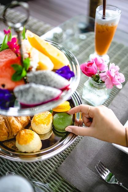 Nachmittagstee mit mini-brioche-häppchen. schöne englische nachmittagsteezeremonie mit desserts und snacks auswahl an süßigkeiten Premium Fotos