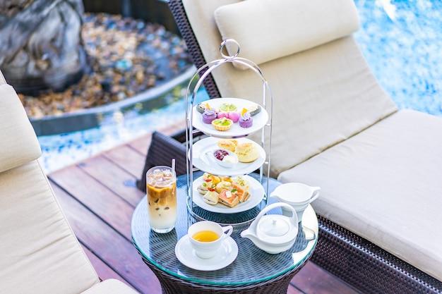 Nachmittagstee-set mit latte-kaffee und heißem tee auf dem tisch in der nähe des stuhls um den pool Kostenlose Fotos