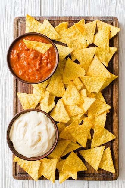 Nachos-maischips mit würzigen tomaten-käse-saucen. Premium Fotos
