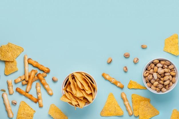 Nachos, pistazien und käsesticks in den weißen schüsseln auf einem blauen hintergrund, draufsicht, ebenenlage Premium Fotos