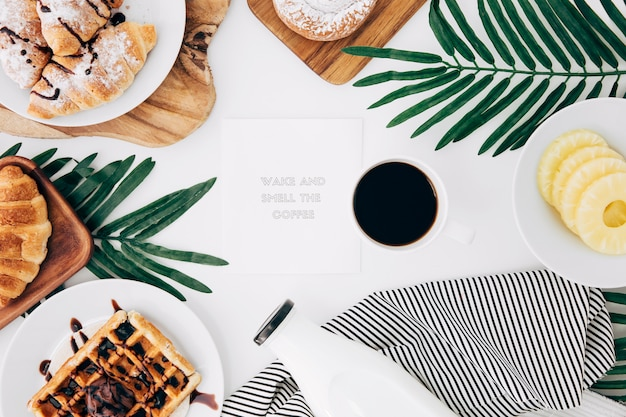 Nachricht auf dem notizblock mit gebackenem frühstück umgeben; kaffee- und ananasscheiben auf weißem schreibtisch Kostenlose Fotos