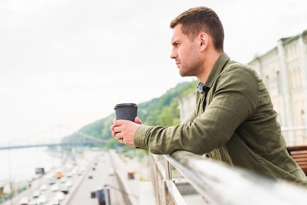 Nachsinnen über den jungen mann, der die wegwerfkaffeetasse schaut stadtansicht hält Kostenlose Fotos