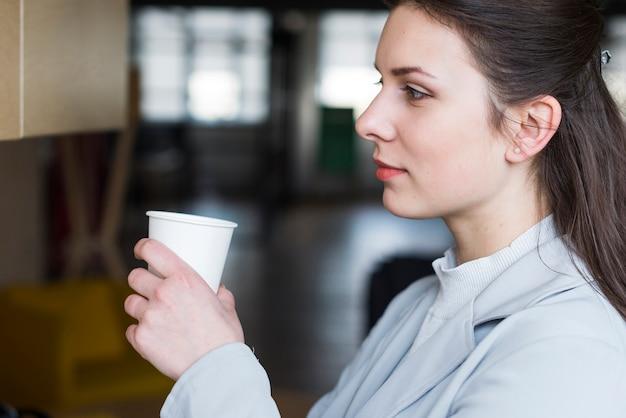 Nachsinnen über die attraktive geschäftsfrau, die kaffeetasse im büro hält Kostenlose Fotos