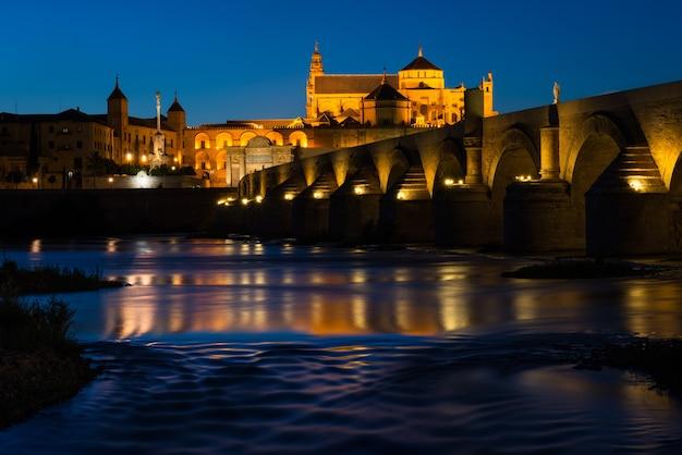 Nachtansicht der berühmten römischen brücke über den fluss guadalquivir und der moscheekathedrale bei nacht in cordoba beleuchtet Premium Fotos