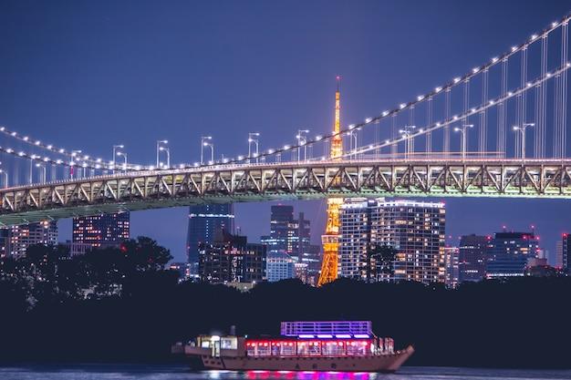 Nachtansicht rainbow bridge und tokyo tower. die kreuzfahrt ist in der bucht von tokyo, odaiba in der nacht, japan, gesegelt Premium Fotos