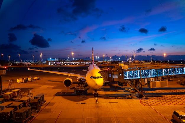 Nachtdämmerung am flughafen mit einem flugzeug Premium Fotos