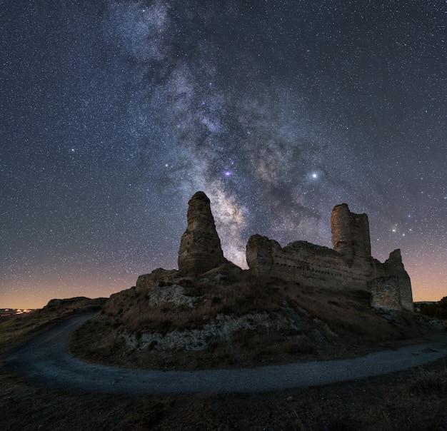 Nachtlandschaft mit der milchstraße über einem alten schloss Premium Fotos